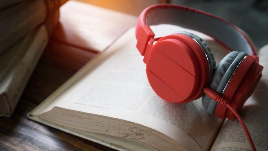 Un paio di cuffie appoggiate su un libro. Il nostro servizio di registrazione personalizzata permette di ascoltare qualsiasi testo