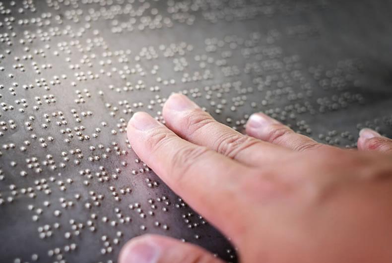 Una mano sfiora i caratteri Braille