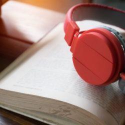 Una cuffia appoggiata su un libro, a voler rappresentare la trasformazione del testo in nero in audiolibro